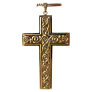 Fourteen karat yellow gold cross with c- scroll adornment on both sides