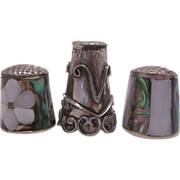 Collection of three thimbles, two abalone shell and scroll design silver