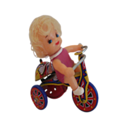Girl on a tricycle wind up tin toy