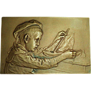 Decorative Bronze Plaque of Boy with Sailing Ship. Art Nouveau appr. 1915