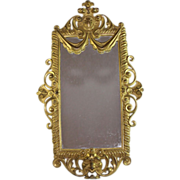 Antique Bronze wall mirror with open worked frame and scrolls