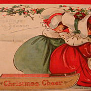 """B.E.B. """"Christmas Cheer"""" Early Postcard Two Ladies in Huge Bonnets, Velvet Dresses and Muffs Pulling Wooden Sled"""