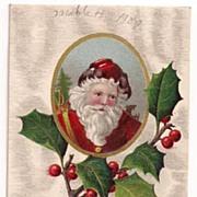 'A Merry Christmas' Santa Head in Cameo on a Holly Bough Postcard 1909