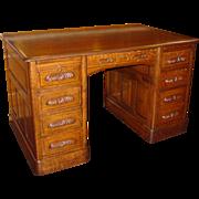 Quartered oak executive desk---raised panels, file drawer, carved pulls